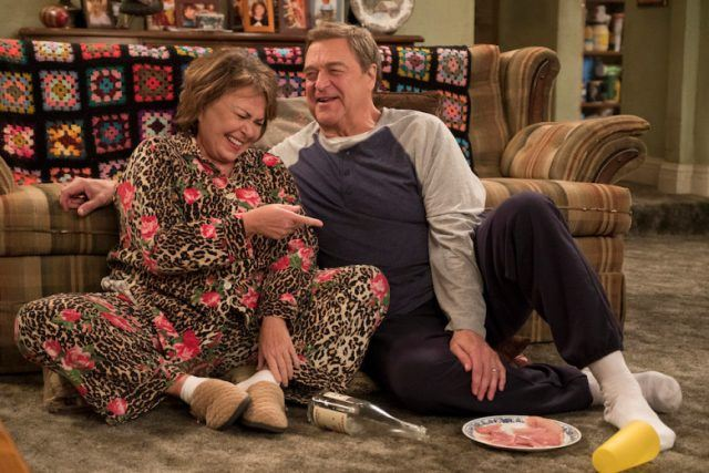 Roseanne and Dan sitting in the living room.