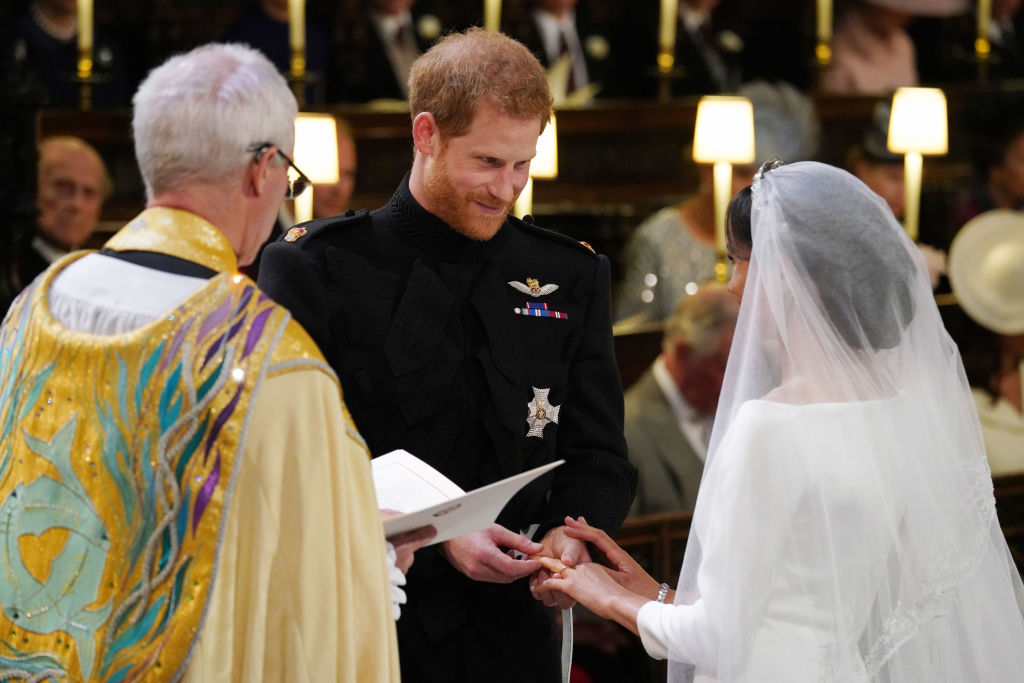Prince Harry places the ring on Meghan Markle's finger during their wedding ceremony.