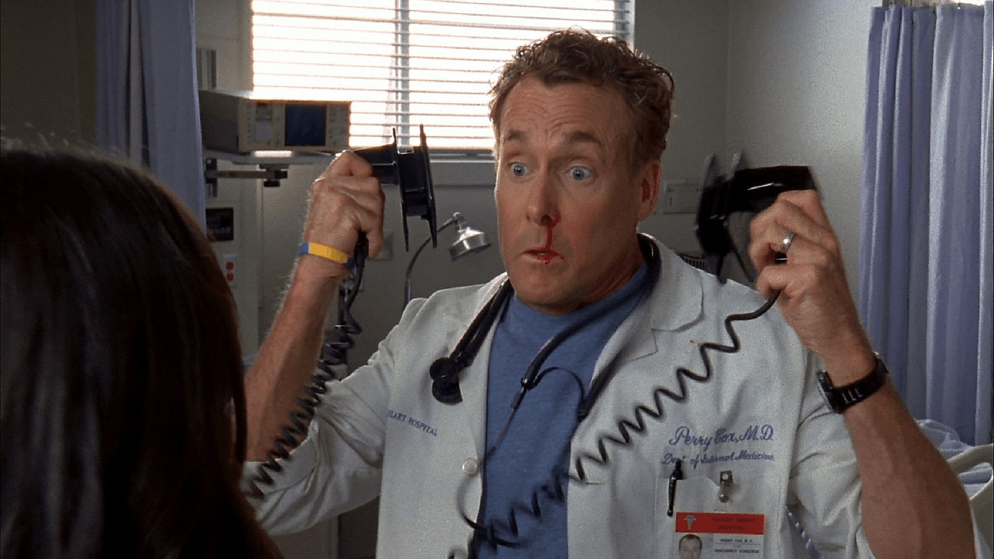 Dr. Cox holding defibrillators on Scrubs
