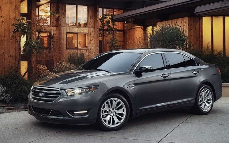 A gray 2018 Ford Taurus parked outside a home