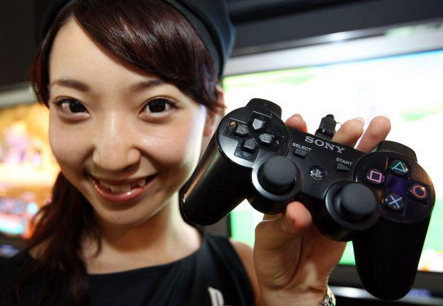 A woman holds the controller of a new PlayStation 3