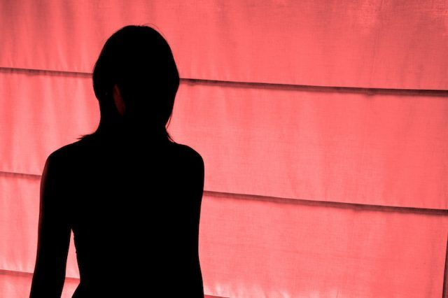 A woman's silhouette seen in front of a red wall.