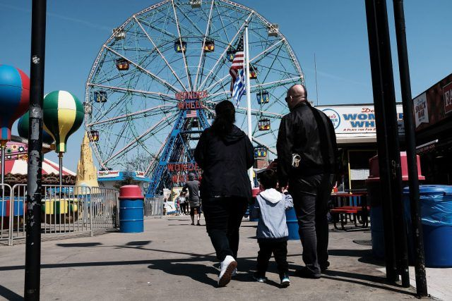 People walk along the boardwalk at Coney Island in New York City