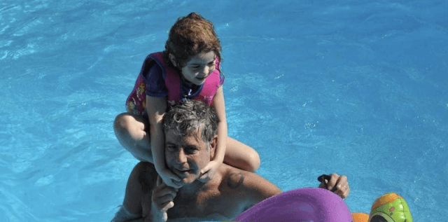 Ariane playing with Anthony Bourdain in a pool.