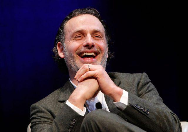 Andrew Lincoln laughing while siting on stage during a press event.