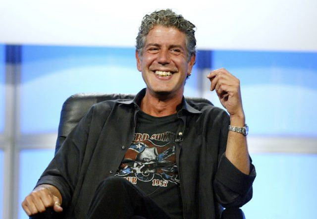 Anthony Bourdain sitting on stage and smiling.