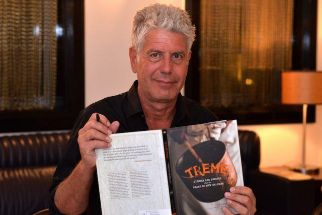 Anthony Bourdain holding up a book.