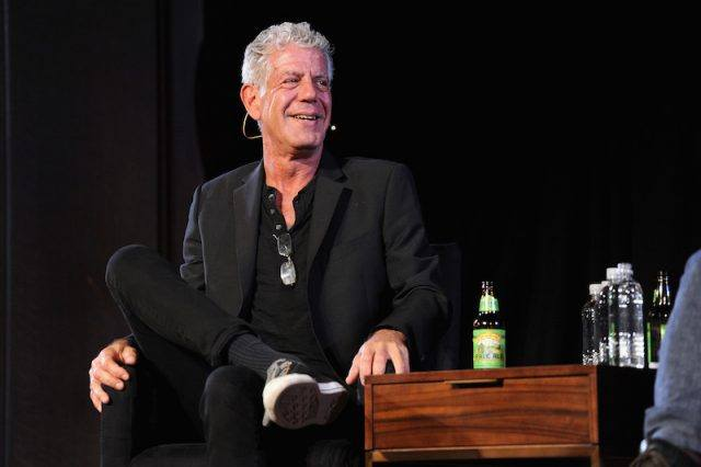 Anthony Bourdain sitting on stage during an interview.
