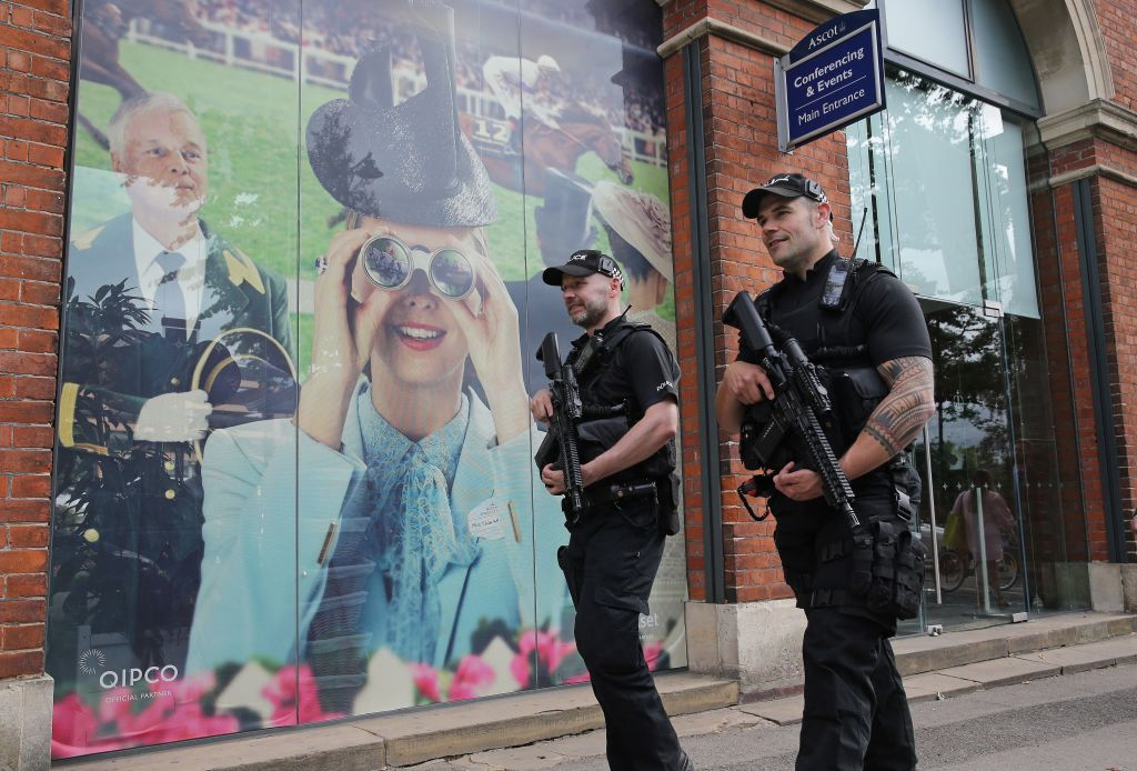 Armed British police officers carry their weapons as they patrol outside the entrance on day one of the Royal Ascot