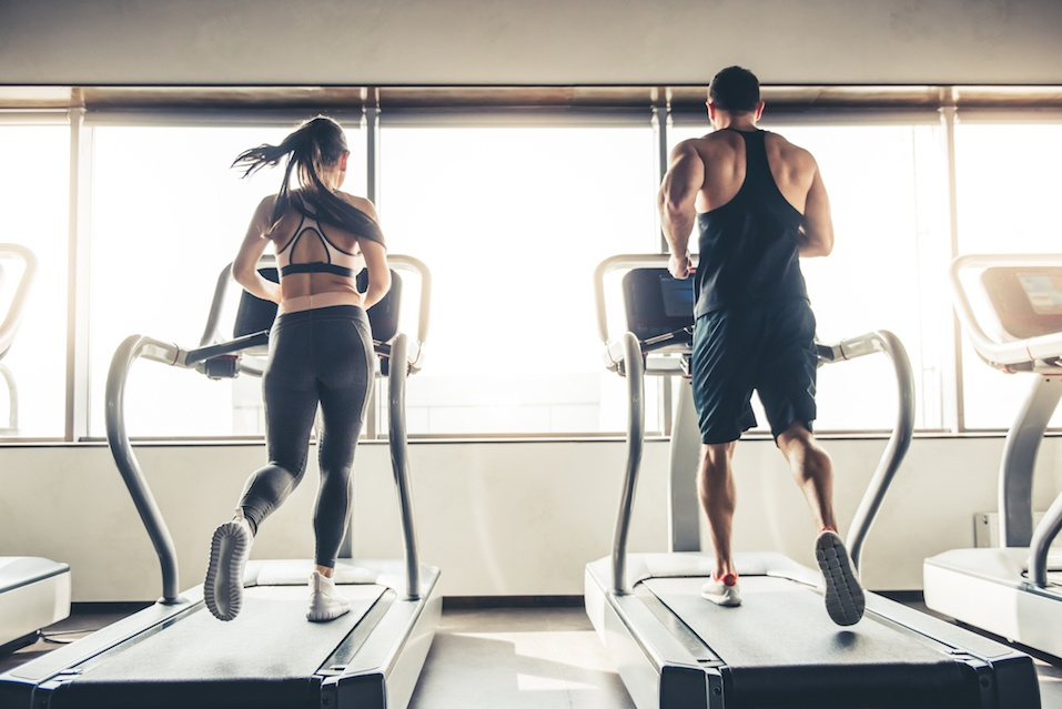 Man and woman running at the gym