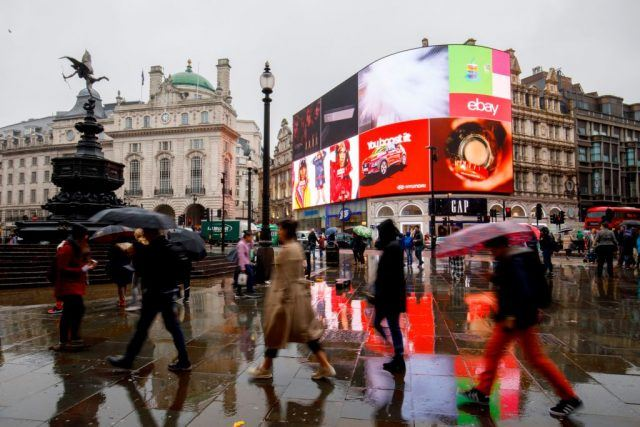 Pedestrians walk past Piccadilly Circus