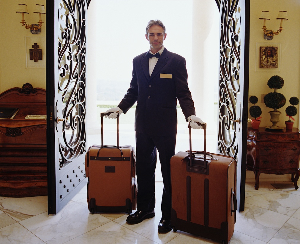 Hotel attendant carrying luggage, portrait