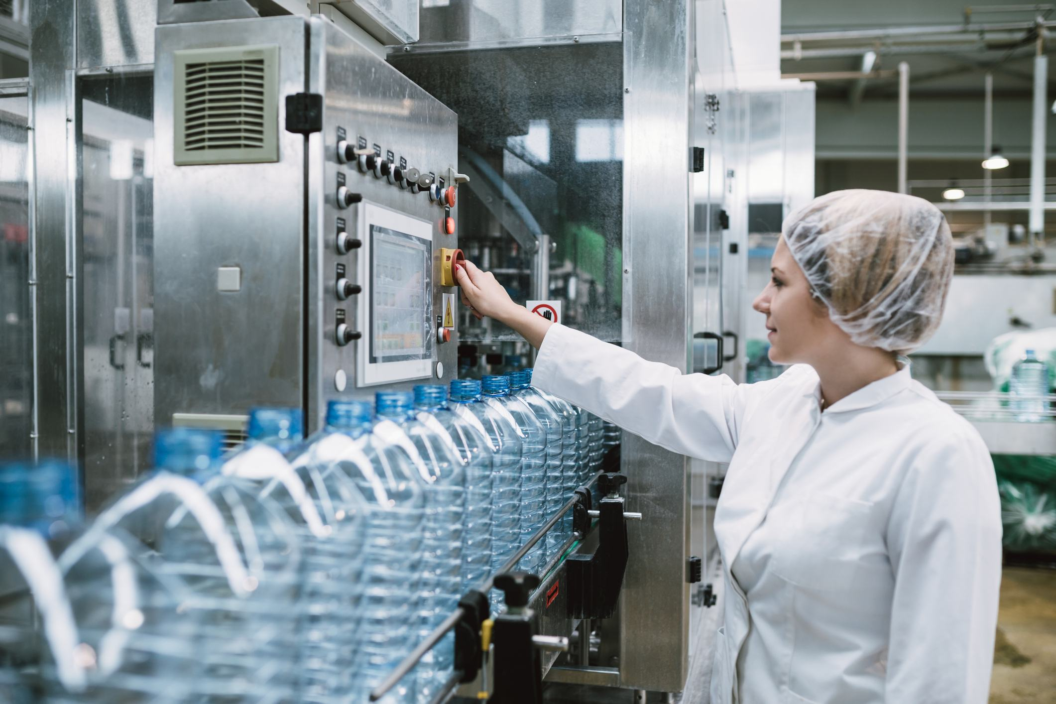 Female bottler packaging water bottles in factory