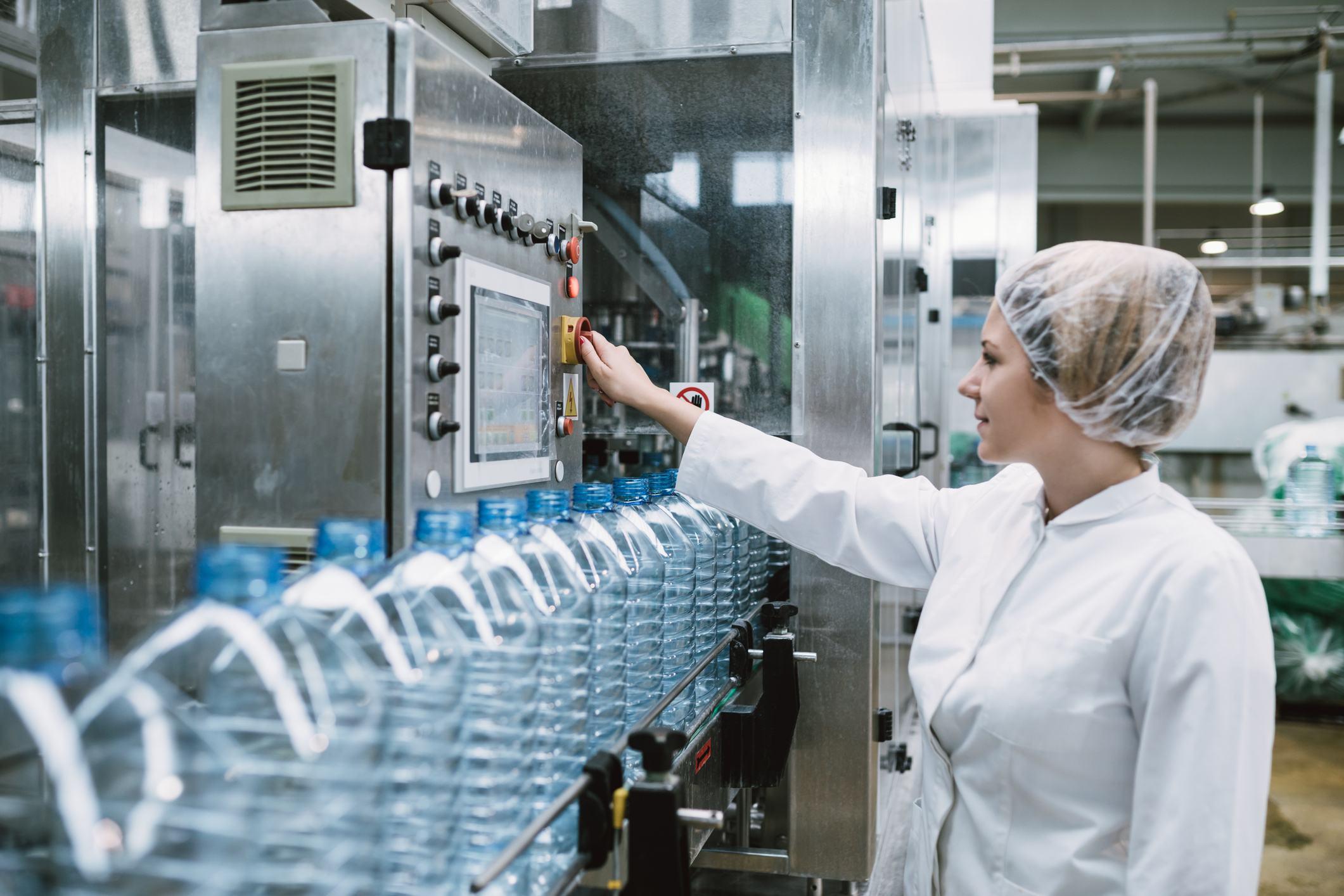 Female bottler packaging water bottles in factory