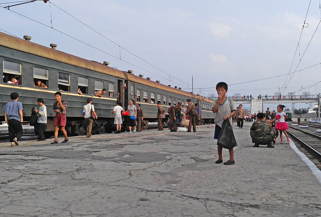 A little boy begs for food on the platform in Hamhung Railway Station