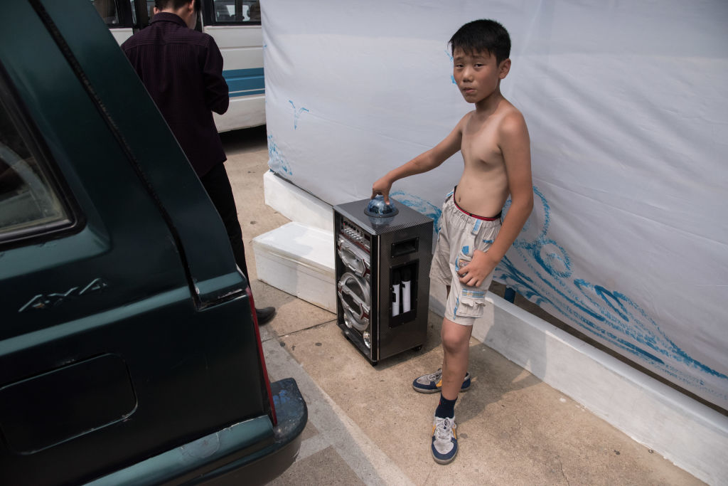 a boy standing with a karaoke machine at the West Sea Barrage beach outside the coastal city of Nampho, southwest of Pyongyang