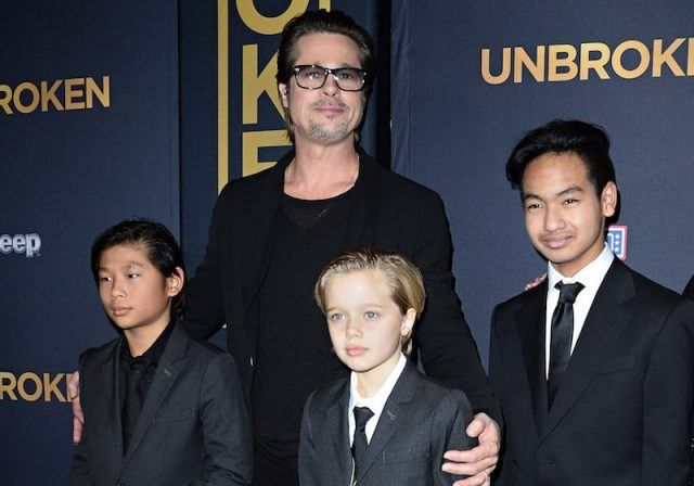 Brad Pitt and his sons on a red carpet.