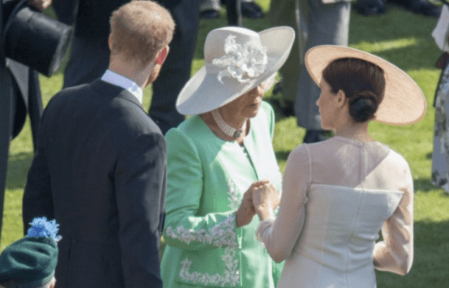 Camilla Parker Bowles and Meghan Markle holding hands.