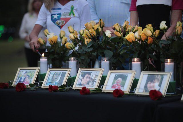 Photos of victims and candles on a table.