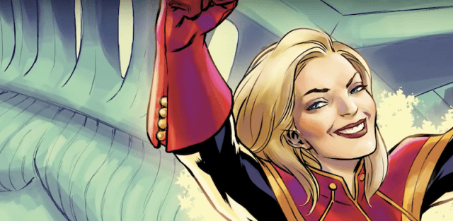 Carol Danvers smiling and raising her arms.