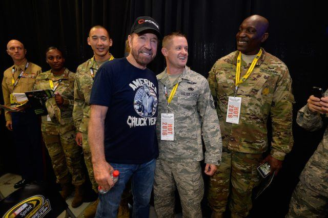 Chuck Norris poses with U.S. military members at the drivers meeting prior to the NASCAR Sprint Cup Series AAA Texas 500
