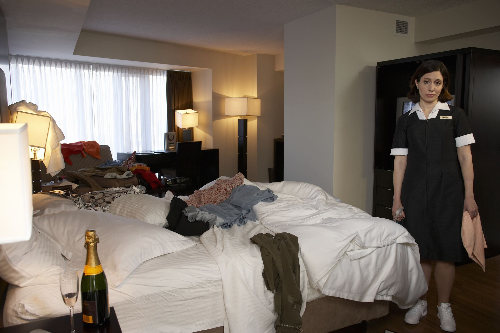 Chambermaid standing in trashed hotel room