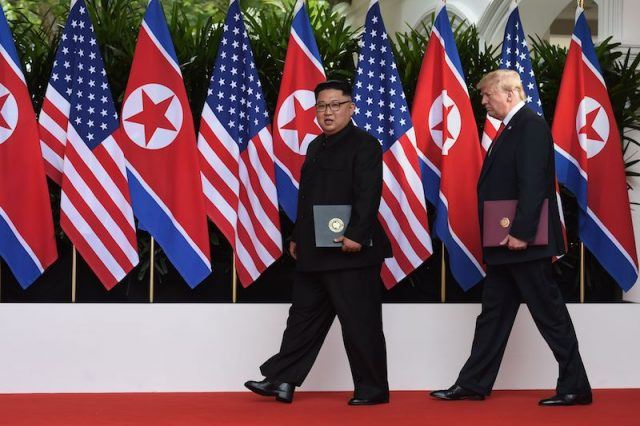 Donald Trump and Kim Jong Un walking in front of flags.