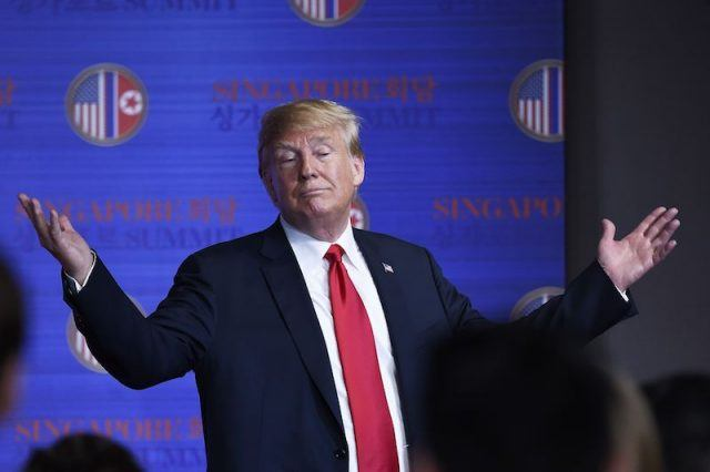 Donald Trump with his hands raised.