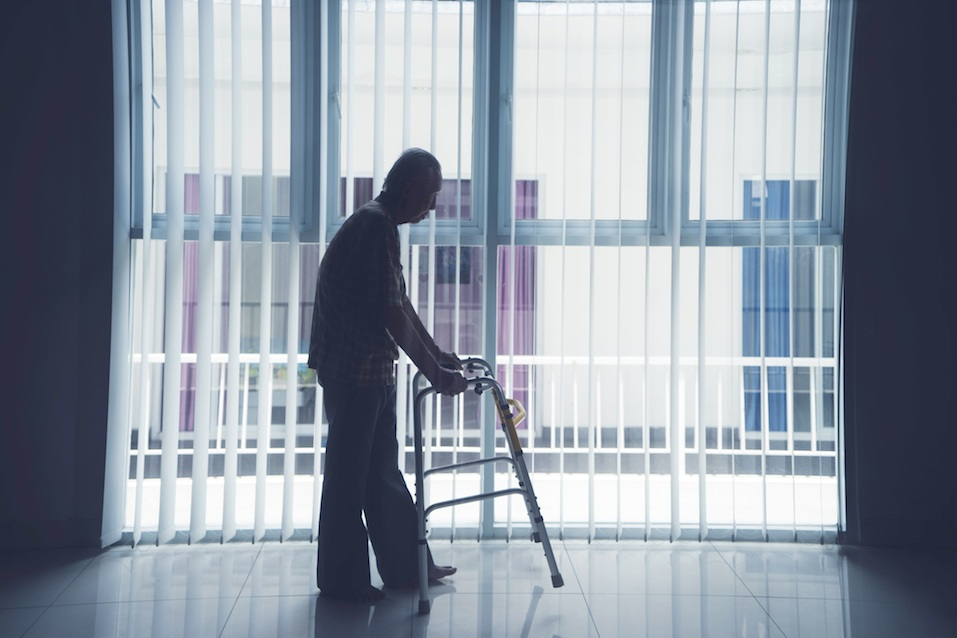 Elderly man walks with a walker near the window