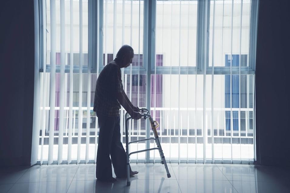 Elderly man walks with a walker near the window