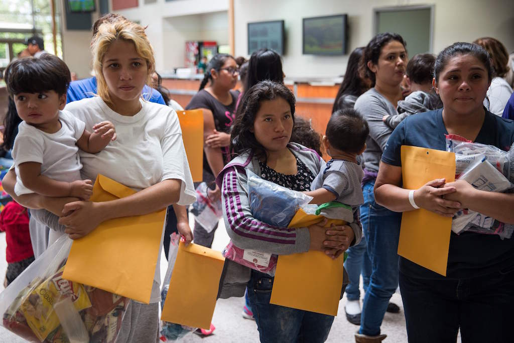 """Immigrants wait to head to a nearby Catholic Charities relief center after being dropped off at a bus station shortly after release from detention through """"catch and release"""" immigration policy on June 17, 2018 in McAllen, Texas. - """"Catch and release"""" is a protocol under which people detained by US authorities as unlawful immigrants can be released while they wait for a hearing."""