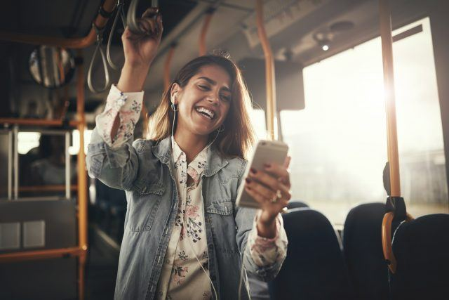 Young woman laughing at her phone