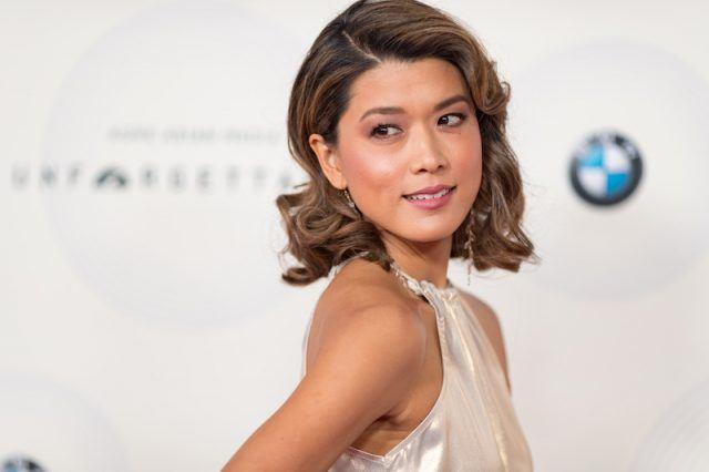 Grace Park posing in a white dress on a red carpet.