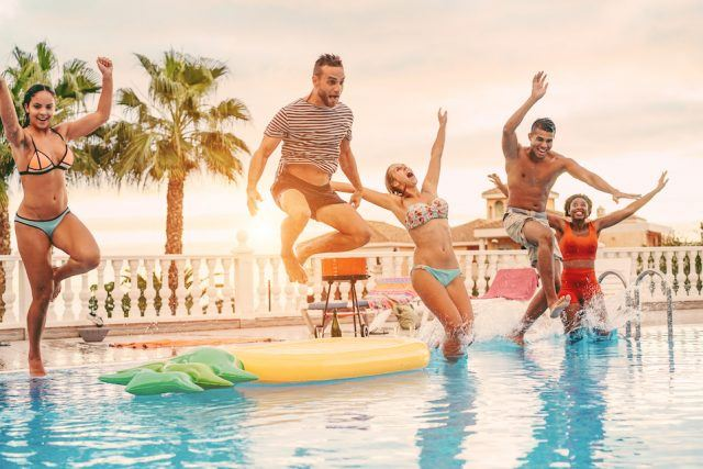 happy friends drinking jumping in pool