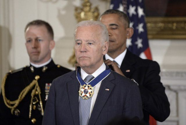 Barack Obama placing medal on Joe Biden.