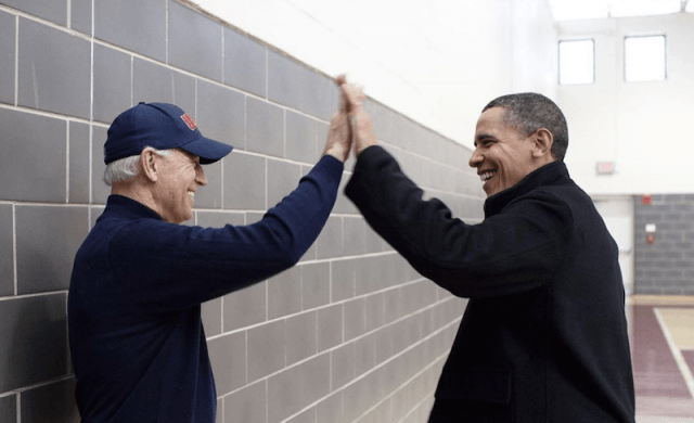 Barack Obama giving a high five to Joe Biden.