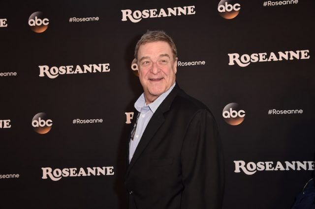 John Goodman wearing a black suit on a red carpet.