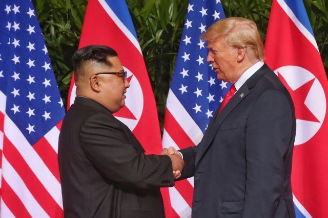 Kim Jong Un and Donald Trump shaking hands.