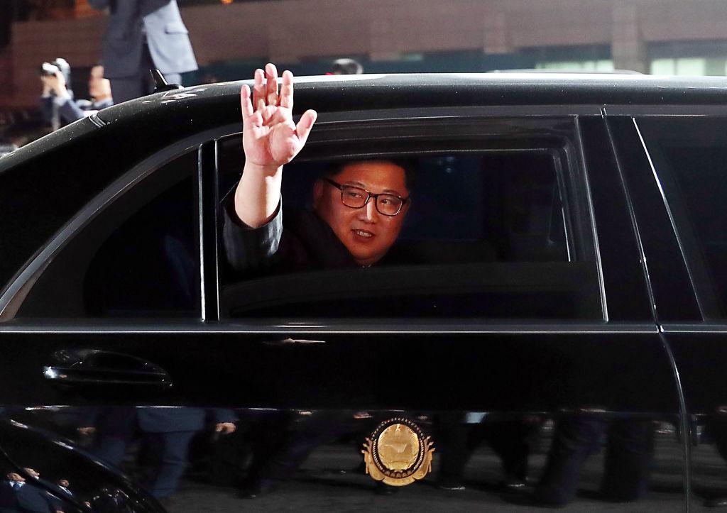 North Korea's leader Kim Jong Un waves in a ca