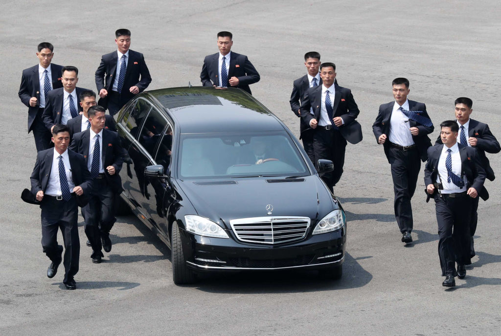 North Korean bodyguards jog next to a car carrying North Korea's leader Kim Jong Un