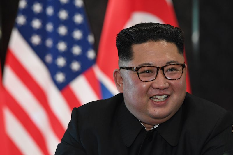 North Korea's leader Kim Jong Un reacts at a signing ceremony with US President Donald Trump