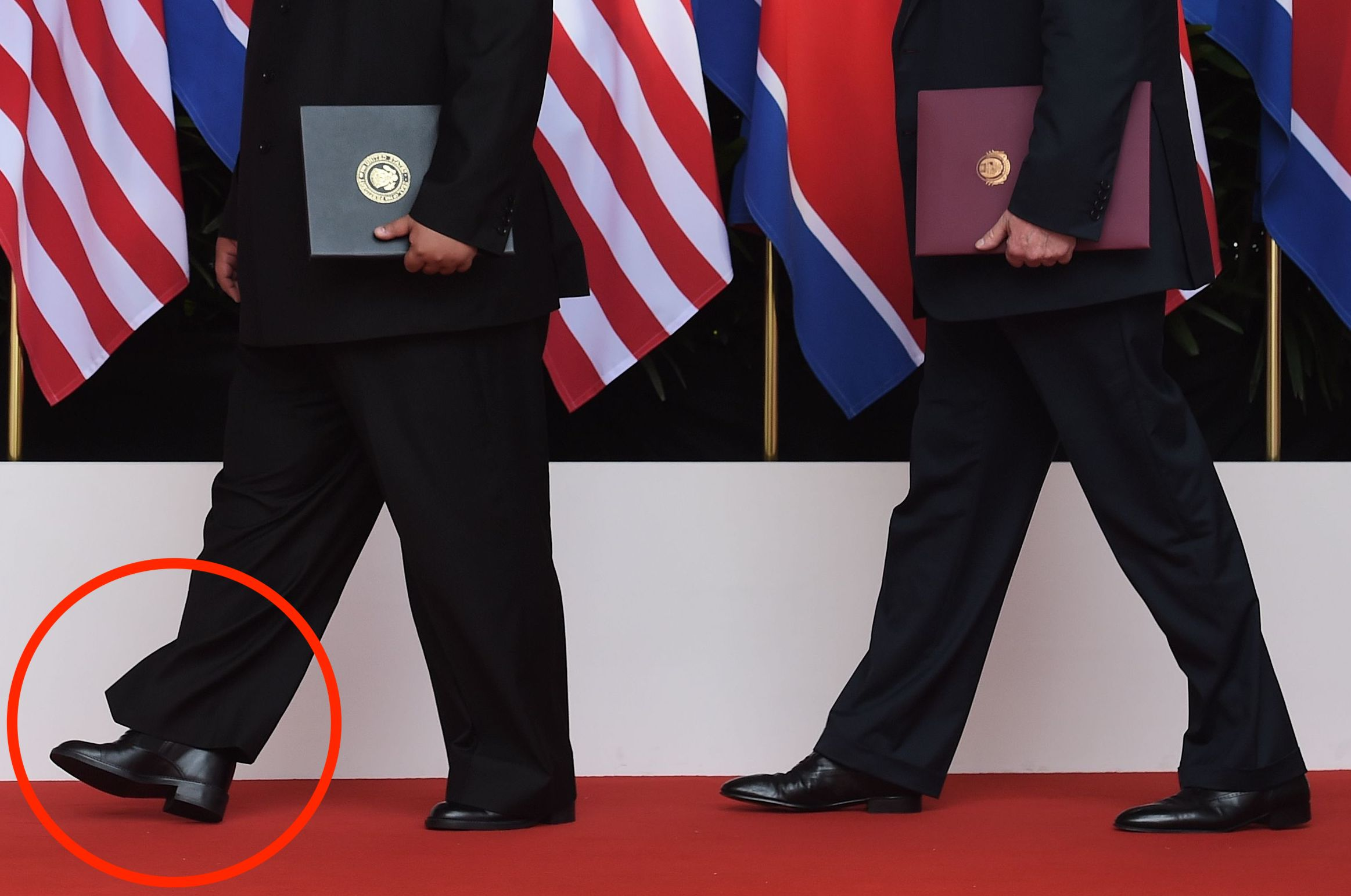 US President Donald Trump (R) poses with North Korea's leader Kim Jong Un focus on shoes
