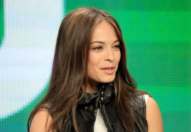 Kristin Kreuk speaking on stage during a CW event.