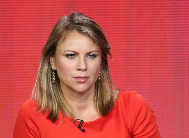 Lara Logan sitting in front of a red background.