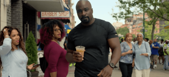 Luke Cage walking down the street as bypasses stare at him.