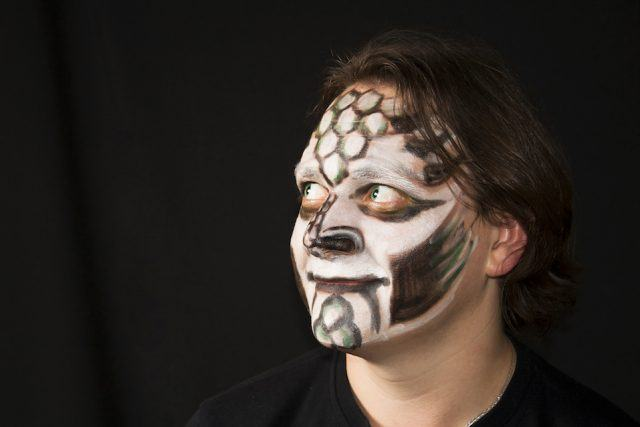 A person sports reptilian face paint.