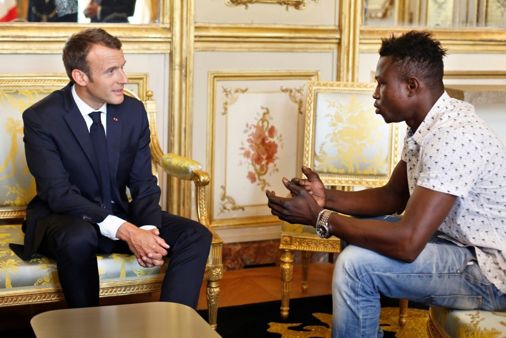 French President Emmanuel Macron (L) speaks with Mamoudou Gassama