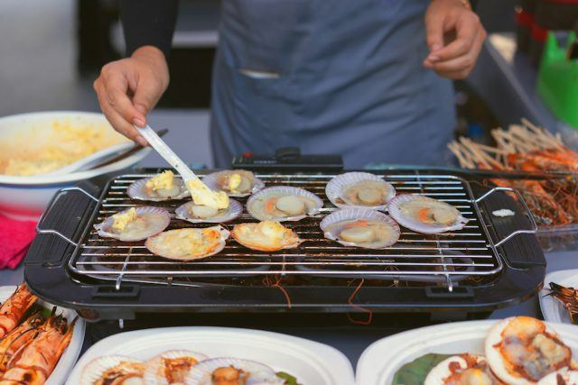 Man cooking the bbq scallops and seafood on a grill