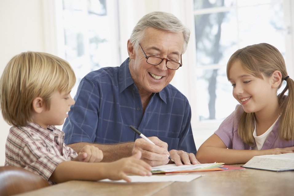 Man helping two kids with homework at a kitchen table