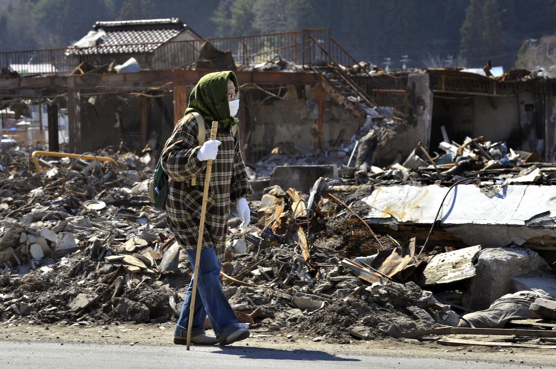 An elderly woman walks amongst tsunami debris